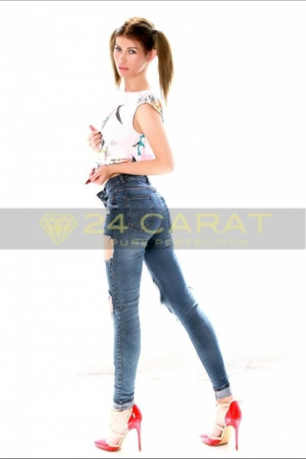 24 Carat Escort Aly poses in a white top and blue jeans with pigtails