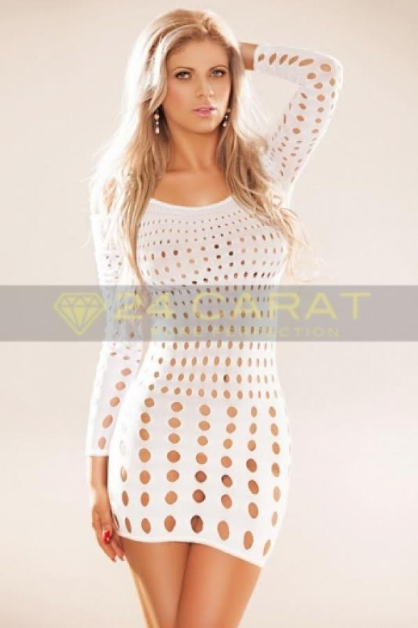 24 Carat Escort Blondie poses in a white polka-dot holed dress