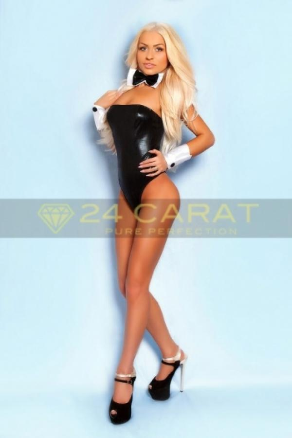 24 Carat Escort Celia poses in a black outfit and black heels