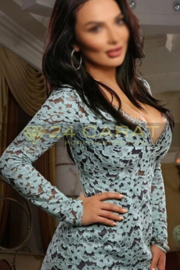 24 Carat Escort Renata posing in a turquoise floral dress