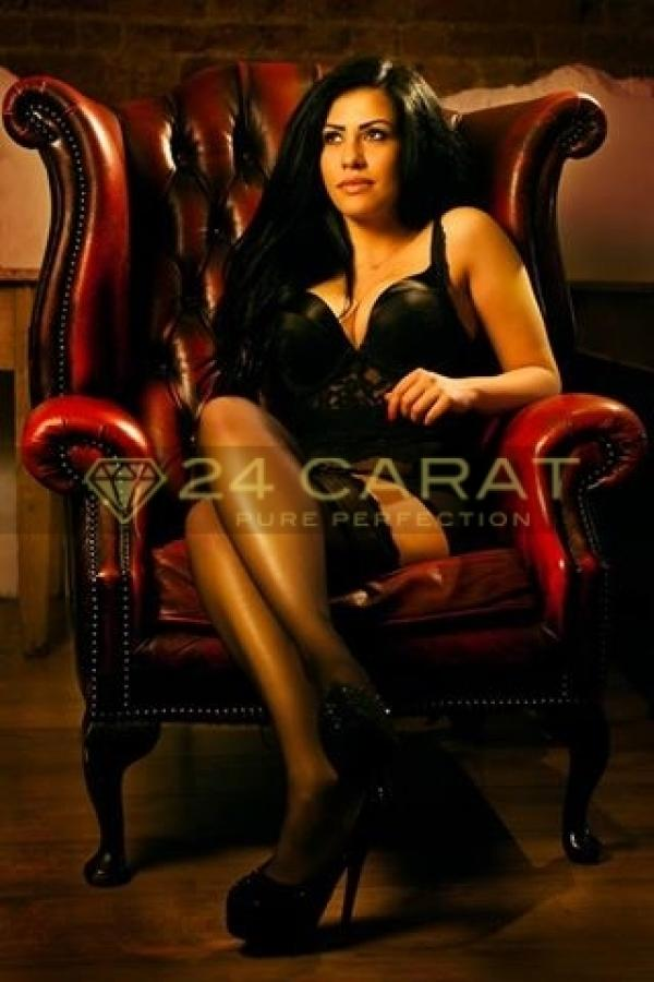 24 Carat Escort Paris sits on a leather chair wearing a black dress, tights and heels