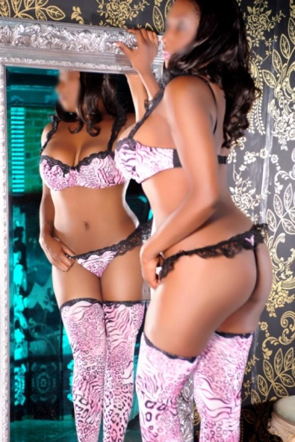 Kaycee admires her reflection wearing pink lingerie including a thong and stockings