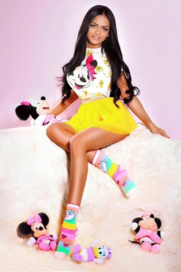 Roxanne poses wearing a Minnie Mouse top amongst disney plush toys