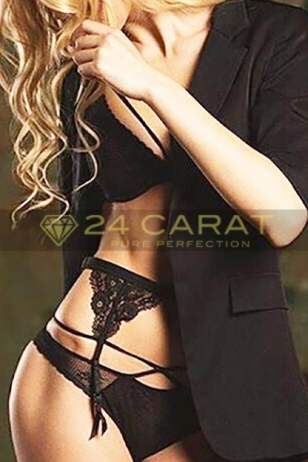 24 Carat Escort Candy opens her black jacket to reveal black panties and bra