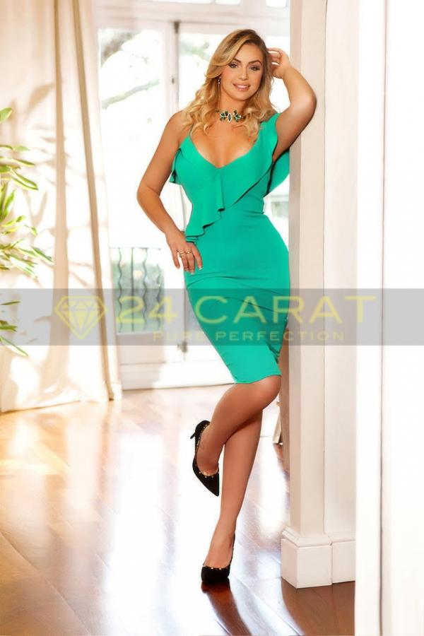 24 Carat Escort Cassia poses in a turquoise-green dress with black heels and choker