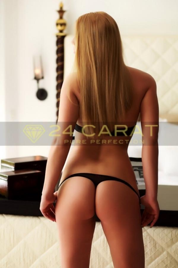 24 Carat Escort Jackeline poses with her back to the camera in black underwear