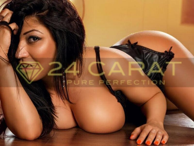 24 Carat Escort Manuela lying on a wooden surface with her breasts out