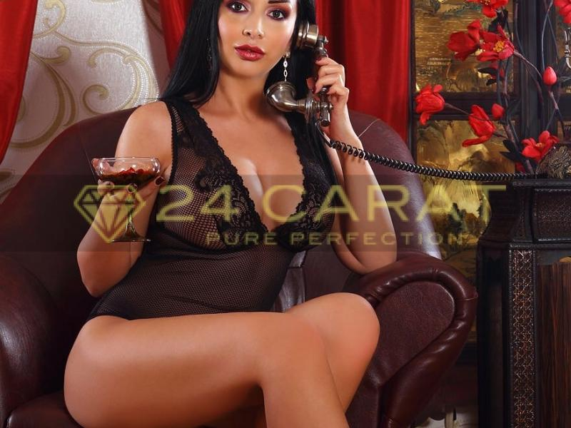 24 Carat Escort Serena sits on a leather chair in a revealing outfit on the phone