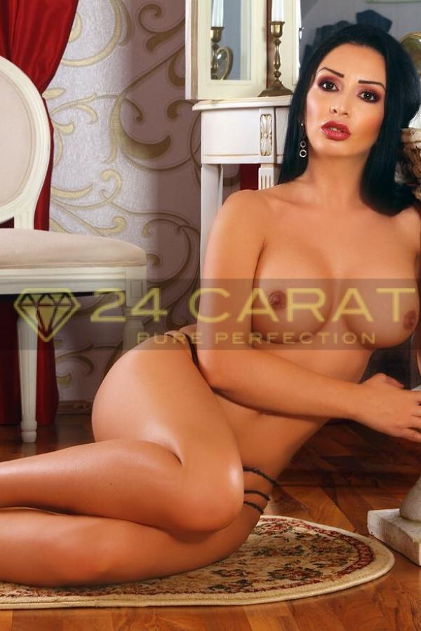 24 Carat Escort Serena sits completely naked on the floor in a gilded drawing room